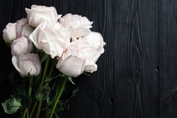 Delicate white roses on black wooden background close up, beautiful light pink flowers bouquet on dark gray wood, birthday greeting card, valentines day, floral border, wedding frame, text copy space
