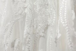 Delicate white wedding dress fabric. Detail close up of lace stitching and embroidery.