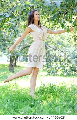 delicate young woman dancing in the morning bright summer orchard