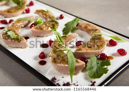 Delicatessen Dish of Lamb Tongues with Green Eastern Dressing on a Rectangular Flat Dish Decorated with Greens, Sauce and Pomegranate Grain