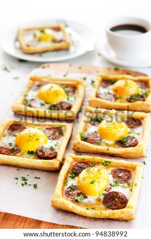 Delicious and appetising egg and sausage tarts garnished with parsley, great for breakfast
