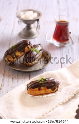 Delicious and beautiful chocolate small cake ekler pastry and tea. Stok fotoğraf ©