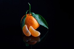 Delicious and beautiful Tangerines. Peeled Mandarine orange and Tangerine orange slices on a Dark reflective surface.