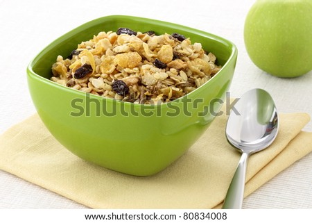 delicious and healthy wholegrain muesli breakfast, with lots of dry fruits, nuts, grains and a fresh apple