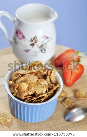 Delicious and nutritious bran flakes cereal in blue bowl with strawberry on wooden cutting board
