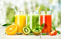 Delicious array of fresh fruit juices served in tall glasses made from liquidised orange, kiwifruit with peppermint, and strawberries for healthy summer treats rich in vitamins