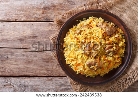 Delicious Asian pilaf on a brown plate. horizontal view from above, rustic style