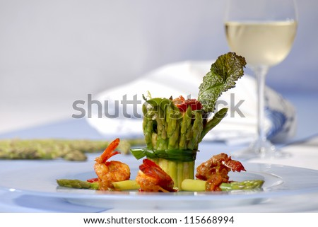 Delicious asparagus dish with a white wine on the table