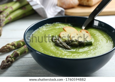 Delicious asparagus soup in bowl on white wooden table, closeup Stock photo ©