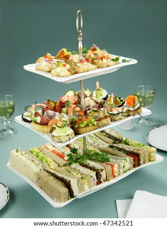 Delicious assorted finger food and sandwiches on a three tier stand.
