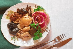 delicious assorted marinated mushrooms on a plate . copy space background