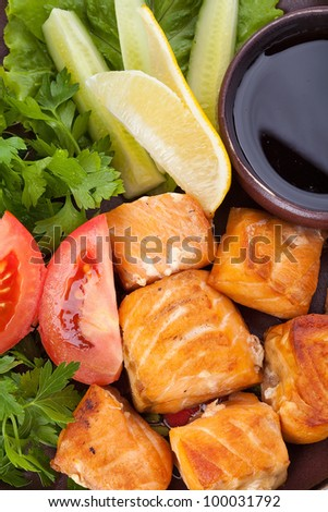 Delicious baked salmon garnished with lemon and tomato for healthy style dinner