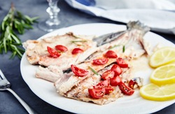 Delicious baked trout with cherry tomatoes, olive oil, lemon juice and fresh rosemary on white plate with lemon slices and fork. Behind blurred glass of red wine, rosemary and towel. Black background