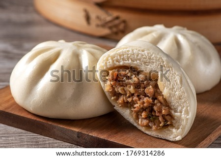 Delicious baozi, Chinese steamed meat bun is ready to eat on serving plate and steamer, close up, copy space product design concept. Stock photo ©
