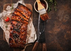 Delicious barbecued ribs seasoned with a spicy basting sauce and served on chopping board