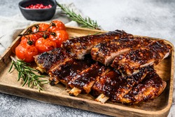 Delicious barbecued ribs seasoned with a spicy basting sauce and served with baked tomatoes. Gray background. Top view