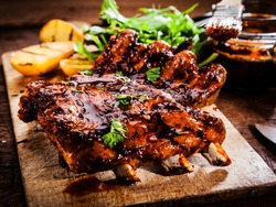 Delicious barbecued ribs seasoned with a spicy basting sauce and served with chopped fresh herbs on an old rustic wooden chopping board in a country kitchen