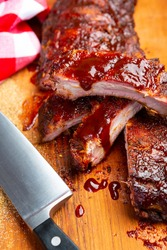 Delicious barbecued ribs seasoned with a spicy basting sauce and spices on an old rustic wooden chopping board in a country kitchen