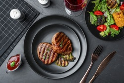 Delicious beef medallions served on grey table, flat lay