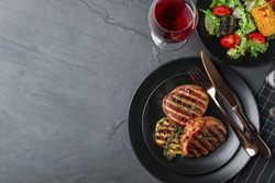 Delicious beef medallions served on grey table, flat lay. Space for text