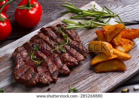 Delicious beef steak with tomato. Meat and rosemary on wooden background. #285268880