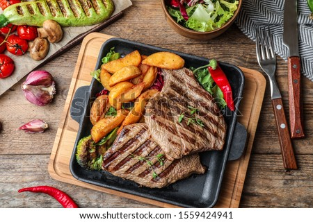 Delicious beef steaks served on wooden table, flat lay