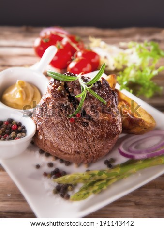 Delicious beef steaks with fresh vegetable and trimmings on wooden table. #191143442