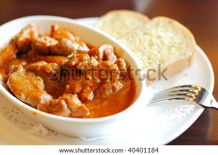 Delicious beef stew with root vegetables and round of bread