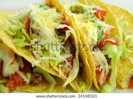 Delicious beef tacos with beef, lettuce, tomato salsa, avocado, grated cheese and sour cream.