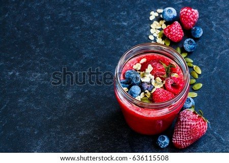 Delicious berry detox smoothie with frozen berries, oats and pumpkin seeds in jar over dark concrete background, selective focus. Dieting, clean eating, healthy eating, vegan, vegetarian food concept.