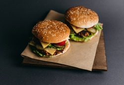 Delicious big juicy burger with tomatoes, cucumbers, cabbage, greens, cheese, cutlet on a gray background. Two sandwiches, fast food. Snack, appetizing, bun with sesame seeds. Serving in restaurant