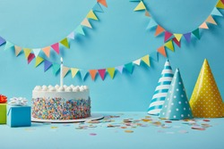 Delicious birthday cake, gifts, party hats and confetti on blue background with bunting