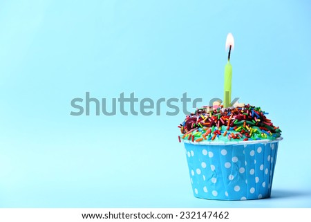 Delicious birthday cupcake on light blue background