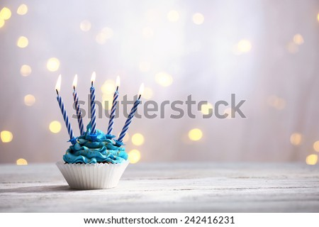 Delicious birthday cupcake on table on light background