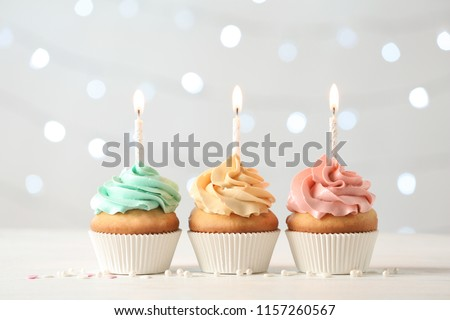 Delicious birthday cupcakes with burning candles on blurred lights background Foto stock ©