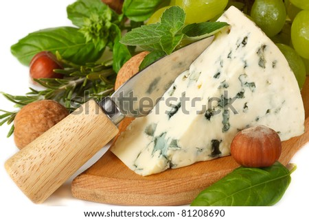 Delicious blue cheese with knife, nuts and spices herbs.