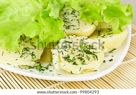 Delicious Boiled Potatoes and Green Salad Leaves on a White Dish on a Bamboo Mat