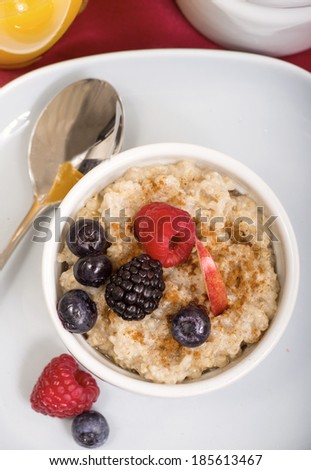 Delicious bowl of freshly made steal cut oatmeal served with fresh blackberries, blueberries, raspberries and apple with cinnamon and maple syrup