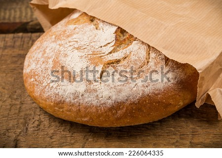 Delicious bread packed in paper on a wood table