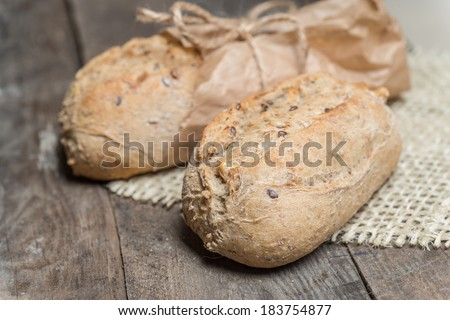 Delicious bread packed in paper on a wood table on sacking