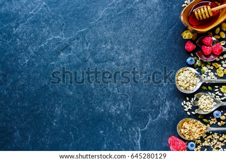 Delicious breakfast concept over slate texture. Frozen berries, seeds, honey and various breakfast cereals - corn flakes, oat flakes, granola and rice crisps on dark backdrop. Top view, horizontal #645280129