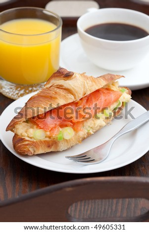 Delicious breakfast of croissant, smoked salmon, coffee and orange juice