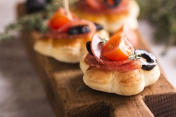 Delicious breakfast sandwiches with salami, tomato, olives and thyme on rustic wooden board