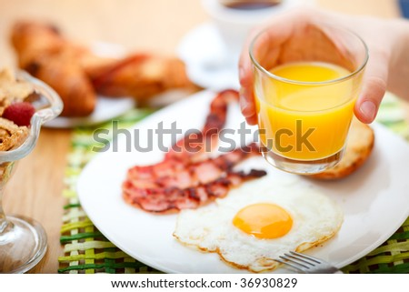 Delicious breakfast served. Corn flakes with berries, fried egg, bacon, toast, croissants, juice and fresh coffee.