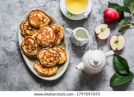 Delicious breakfast, snack - apple pancakes, green tea, fresh apples, cream on a gray background, top view
