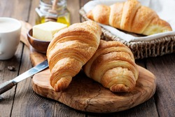 Delicious breakfast with fresh croissants and coffee served with butter and honey.