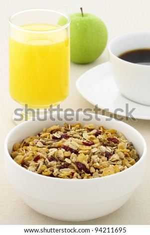 delicious breakfast with orange juice, hot coffee, fresh apple and a healthy bowl of cereal.