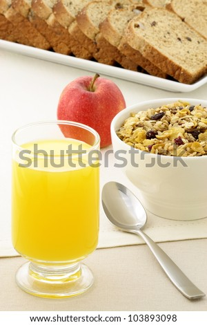 delicious breakfast with orange juice, whole grain bread,fresh apple and a healthy bowl of cereal.