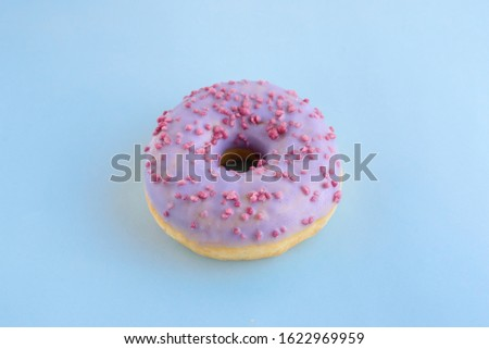 Delicious bright juicy purple one sprinkled donut for a sweet tooth on a blue background. Close-up selective focus. Top view, unhealthy baked goods with sugar.