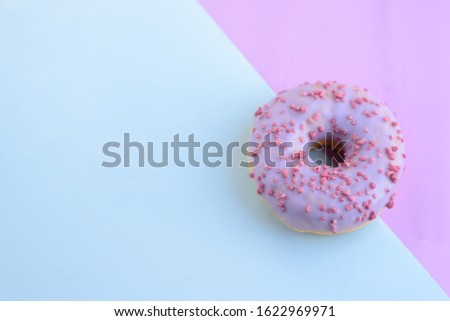 Delicious bright juicy purple one sprinkled donut for a sweet tooth on a purple and blue background. Close-up top view, unhealthy baked goods with sugar. Free space for text